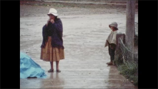 1970s: Man and woman walk down street. Woman and child stand outside, woman looks under blanket.