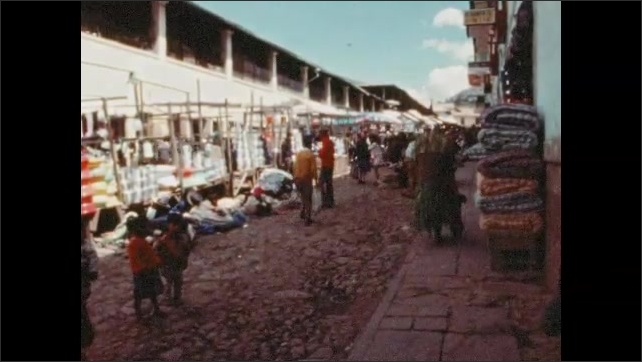 1970s: People walk around street market. Children. Man in suit walks down street.