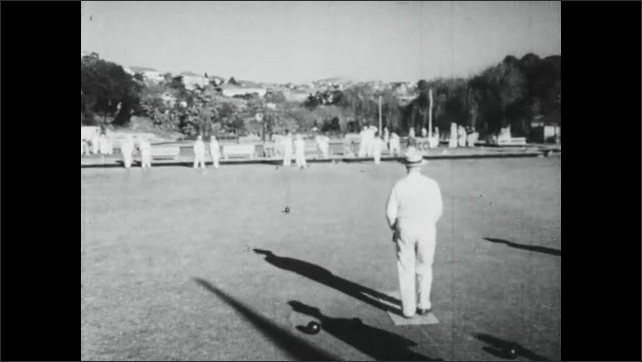 1940s Australia: City.  Women play tennis.  Old men play bocce ball.