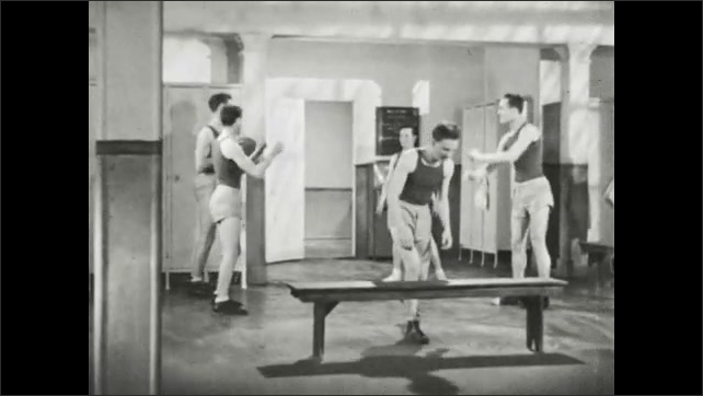1940s: UNITED STATES: men pass ball in changing room. Man lies on bench. Man throws ball.
