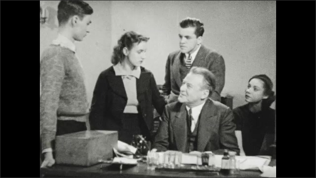 1940s: UNITED STATES: lady talks to man at desk. Medical students talk to professor at desk.