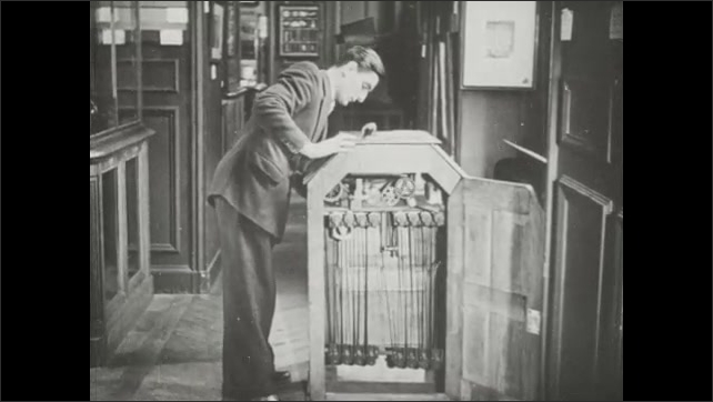 1940s: Man walks up to Edison kinetoscope and looks through the viewfinder. Muscleman poses in the film.