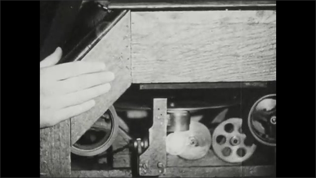 1940s: Muscleman poses in the Thomas Edison kinetoscope, flexing his muscles. Man looks through the kinetoscope as the reels and film moves in the cabinet below.