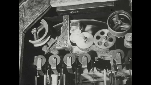 1940s: Reels and film moves in the cabinet below a kinetoscope. Filmstrip passes in front of a lamp. Diagram of film strip.