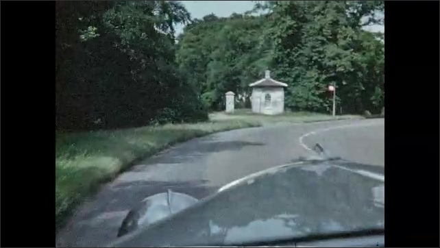1940s: GREAT BRITAIN: view of road from car. Green fields seen from car window. Houses by road