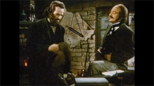 1950s: Men in period costumes talk in office. John Sutter talks to man in office.
