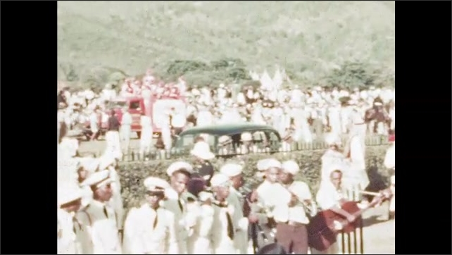 1950s: Large crowd of people and performers in different costumes.