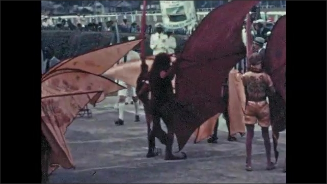 1950s: Performers in bat costumes with large wings dance in front of crowd.