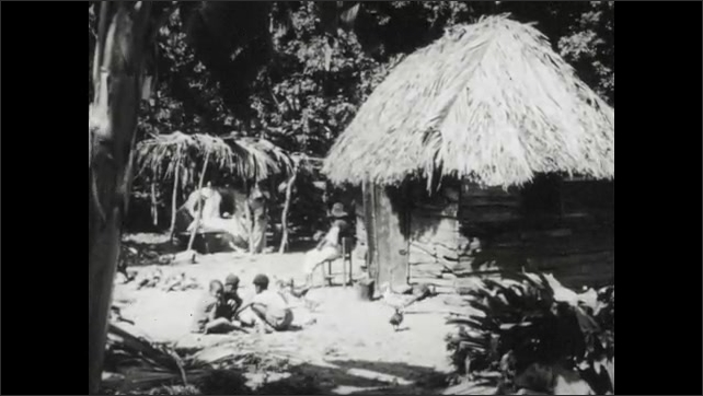 1950s: Men carry rowboat onto beach near ocean bay. Family sits outside grass hut on tropical island. Women wash cloths in river. Man repairs fishing net.