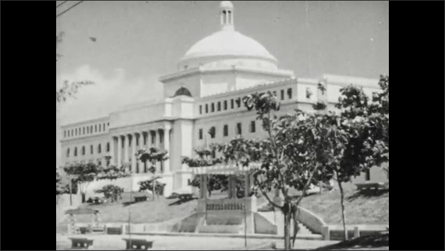 1950s: Soldiers carry rifles and march on walls of castle. Title placard. Trees sway near capitol building in San Juan. Pedestrians and cars navigate narrow city streets.
