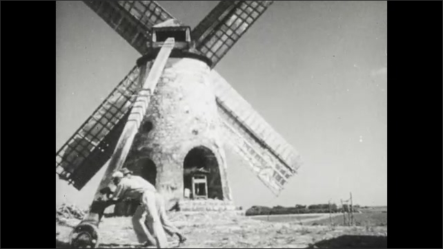 1950s: Title placard. Men and women turn direction of windmill in field. Blades of windmill spin in breeze.