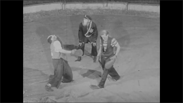 1940s: clown in police uniform hits bell with hammer, clowns swing at and slap each other with large mitts in circus ring, clown slaps police clown, who falls down, clown slaps clown, clown falls down