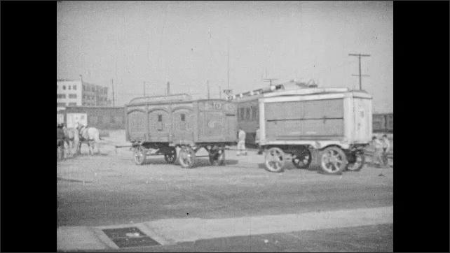 1940s: UNITED STATES: children peep through gaps on circus wagon. Circus workmen sort out tent poles.