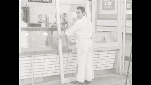 1940s: Women eat in restaurant. Man walks down street. Man installs door.