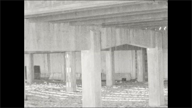 1940s: Man walks under the boardwalk. Boys runs under the boardwalk. People walk around boardwalk shops.