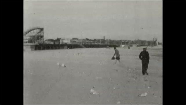 1940s: People swim in ocean. People walk on beach.