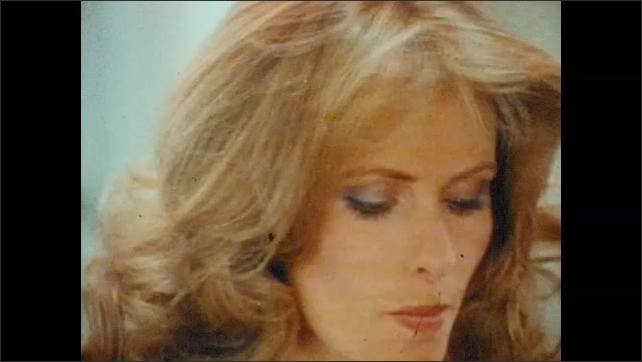 1970s: UNITED STATES: lady runs hand through hair. Lady puts on make up with sponge. Lady puts on lipstick.