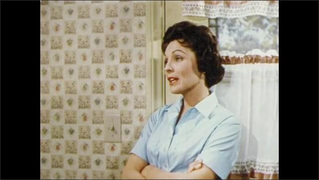 1950s: UNITED STATES: man installs telephone in kitchen. Lady talks to man in kitchen