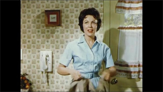 1950s: UNITED STATES: lady talks on telephone. Lady takes off apron. Lady enters room. Flowers in hallway.