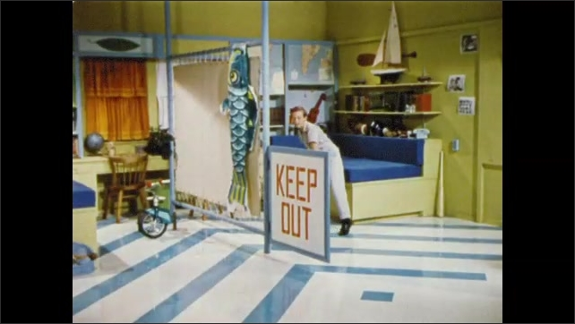 1950s: UNITED STATES: boy in bedroom. Map shutters on wall. Boy pulls down table. Boy bounces on bed.
