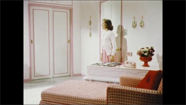 1950s: UNITED STATES: girl goes upstairs. Girl sees new bedroom. Pink bedroom and cushions. Closet of clothes.