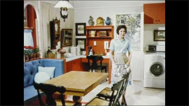 1950s: UNITED STATES: lady looks around new kitchen. Furniture in family dining area. Rug under table.