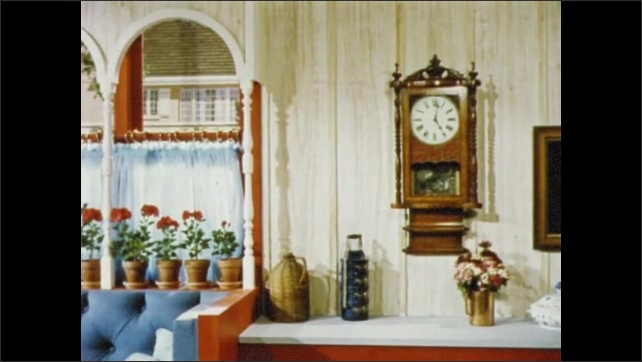 1950s: UNITED STATES: rug under table. Man talks to lady in kitchen. Arches on window. Telephone on wall rings. Lady answers phone