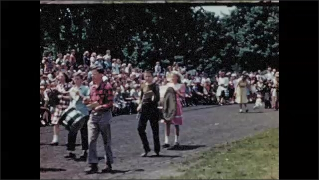 1950s: Dogs sit in row while owners back away.  Owners and dogs walk in parade.  Spectators.