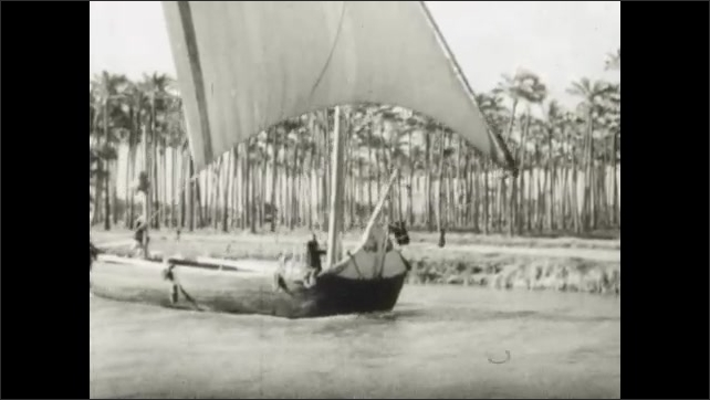 1950s: Man guides oxen through field. Boat sails down canal. Teepees line canal.