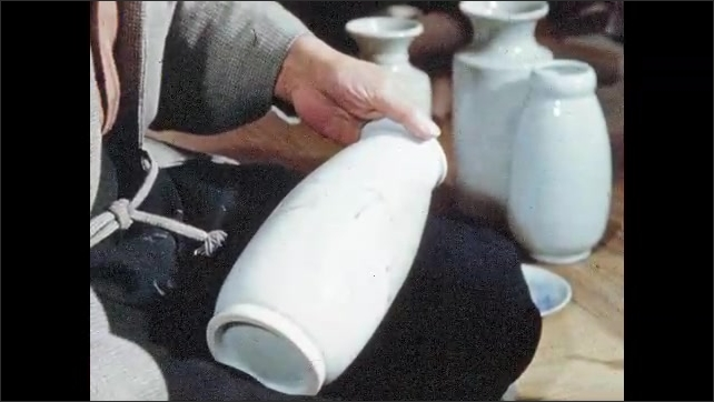 1950s JAPAN: Man sits at potters wheel, turns pottery. Man paints pottery.