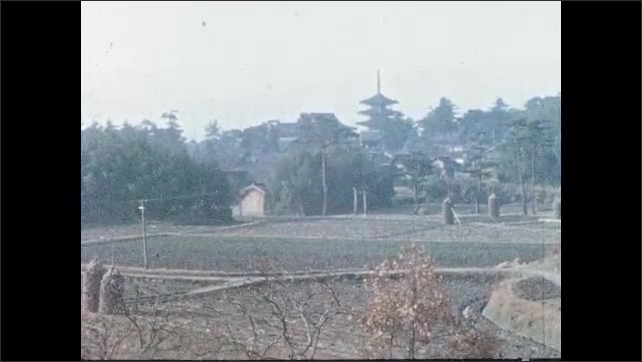 1950s JAPAN: Japanese paper lantern. Field. People walk by Buddhist temple.