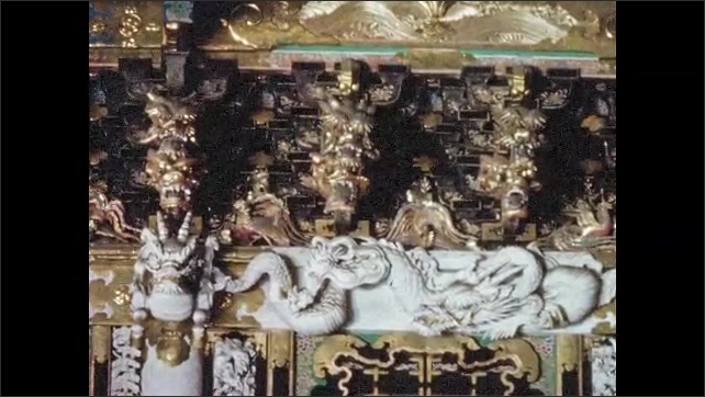 1950s JAPAN: Elaborate sculptures and decorations on Toshogu shrine. Man takes picture at shrine.