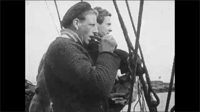 1950s: Men on boat haul in fishing nets.  Man smokes pipe.  Captain gestures.