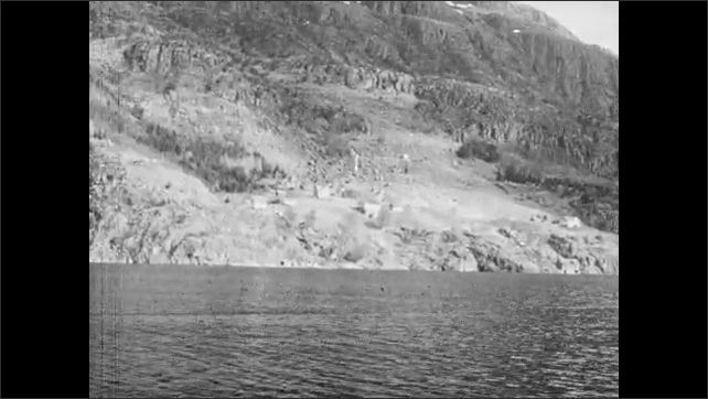 1950s: Mountains.  Water.  Boy and man on small boat.  Man smokes pipe.  Farm.