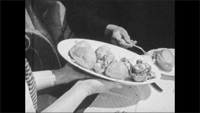 1950s: Dining room.  Family eats dinner.  Mother serves food on platter.