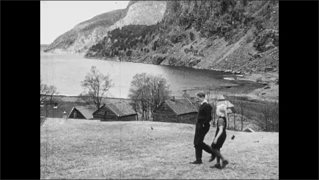 1950s: Flowering tree.  Fly.  Farm.  Mountains.  Sea.  Boy and girl walk along.  Boy kicks boot into muddy ground.