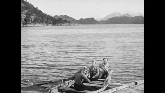 1950s: Teenage girl rows boat with children.  Mountain.  Sea.  Boat lands.  Children get onto dock.  Boy helps girl.  Young woman waves.
