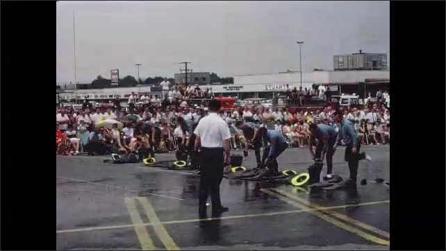 1960s: UNITED STATES: fire truck drives in front of crowd. Pet put on fire kit. Men race to get dressed in uniform.