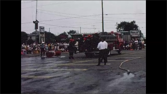 1960s: UNITED STATES: Fire men raise arms. Fire department run towards truck. Firemen run with hose.