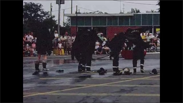 1960s: UNITED STATES: fire men run towards uniforms on ground in race. Men dress in fire uniforms.