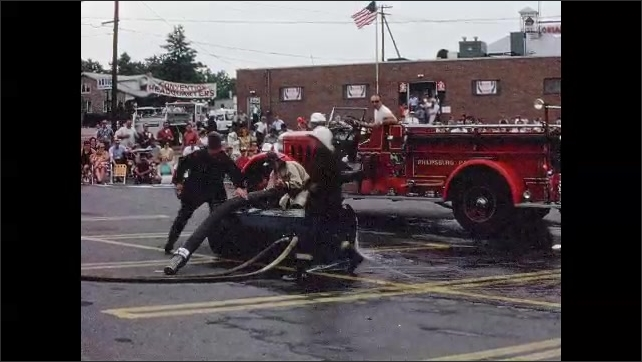 1960s: UNITED STATES: Fire men run to truck, Men fill truck with water. Men spray hoses