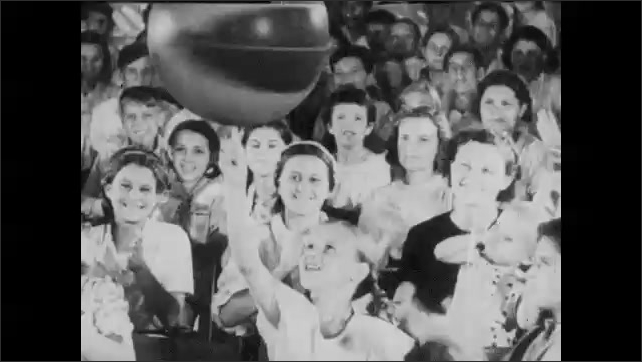 1940s: UNITED STATES: ball rotates on end of man's finger. Girl with spinning ball. Man throws and catches toy on ball. People in crowd clap and smile.