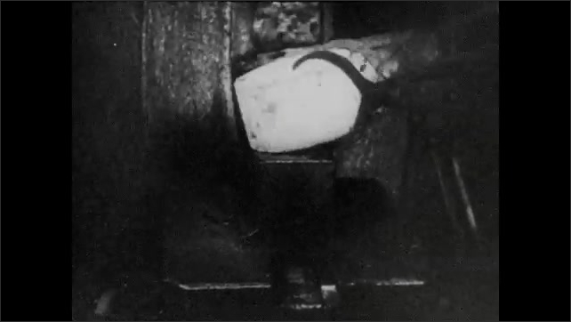 1940s: UNITED STATES: furnace operator stokes fire. Metal and tongues in furnace. Cooling screen of running water.