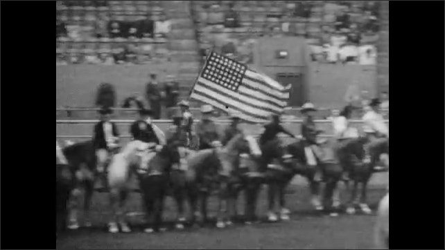 1950s: People hold flags and ride horses around arena. Crowd watches.