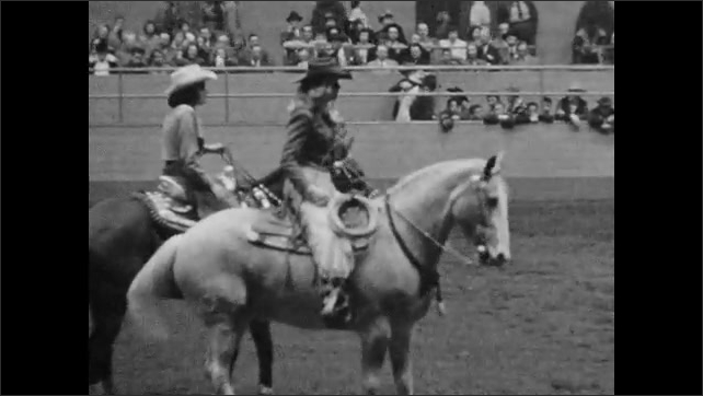 1950s: Girls sit on horses in arena, wave. Men ride horses into arena. Man jumps off horse, tackles small bull.
