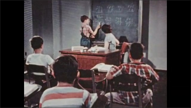 1950s: UNITED STATES: students raise hands in class. Teacher at Boystown school.