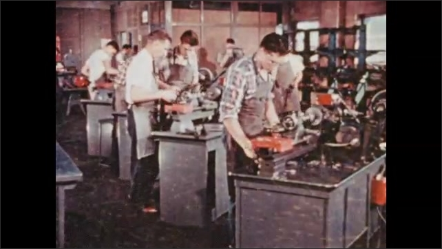 1950s: UNITED STATES: boys learn mechanics at school. Students work with machines in classroom. Vocational training for boys.