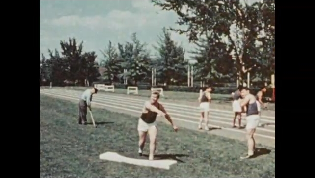 1950s: UNITED STATES: boys run out of building. Boy throws discus. Boys run on track. Boys learn to play American football