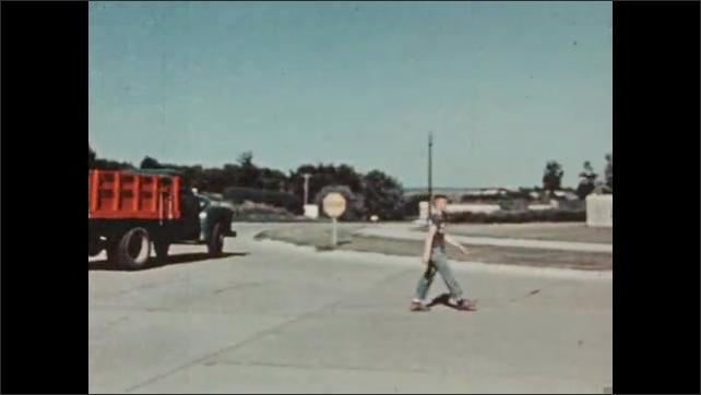 1950s: UNITED STATES: truck on street. Boy arrives at school. Boy walks along path.