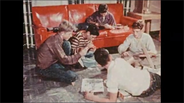 1950s: UNITED STATES: boys talk on grass. Students relax in room. Boys play game in yard.
